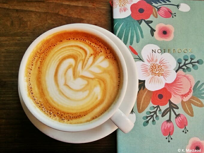 Coffee and a notebook on a wooden table
