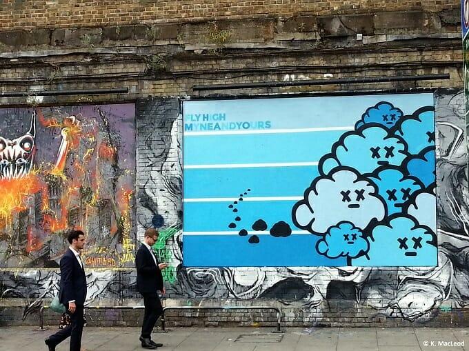 People walking past street art in Shoreditch
